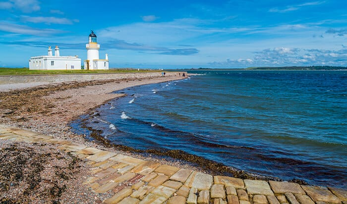 Chanonry Point - blue coastal waters with a white light house in the distance