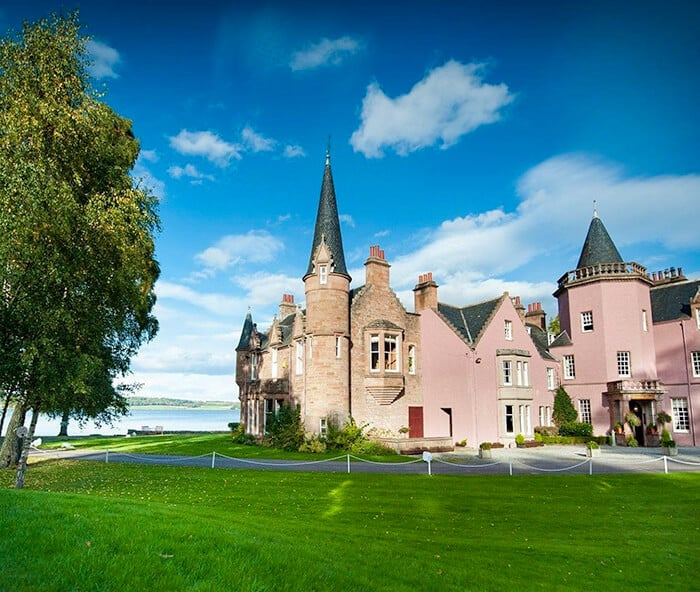 Powder and light pink castle hotel with bright blue skies on a green bed of grass