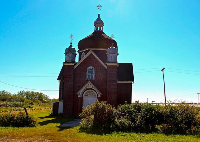Saskatchewan Ghost town Insinger red brick Ukranian Orthodox Church with boarded up windows and aged wood roof top