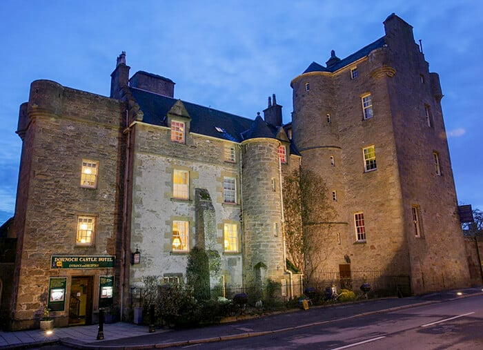 Large Castle Hotel with lights on inside rooms at night. One of the places you can stay in a Haunted Castle Overnight in Scotland