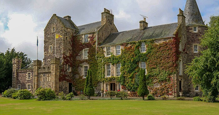 Large castle covered in vines, bushes and green and red leaves. Stay in a Haunted Castle Overnight in Scotland