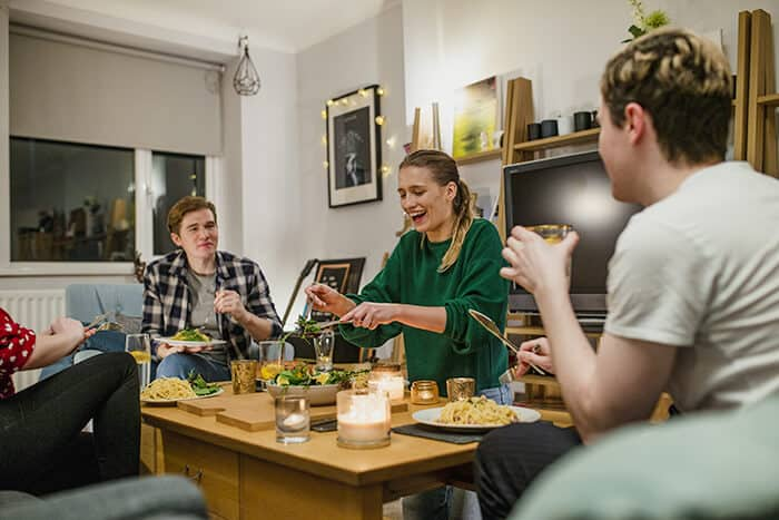 Group of people enjoying food while sitting in the living room