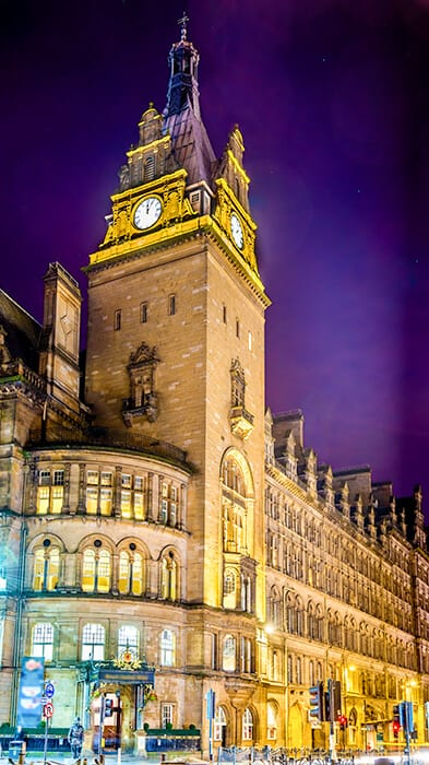 The historic and haunted hotel in Scotland - the Grand Central Hotel in Glasgow with a huge clock tower at night. Haunted Hotels in Scotland.