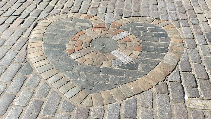 The Heart of the Midlothian - a heart made of bricks on the brick pavement marks the site witches in Scotland stayed at in the Old Tolbooth Prison
