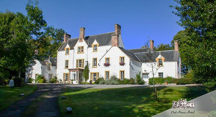 Large white house hotel surrounded by bright green trees. Haunted Hotels in Scotland.