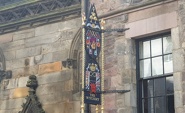 "A sign fixed to the haunted hotel building saying ""The Witchery"" Haunted Hotels in Scotland"