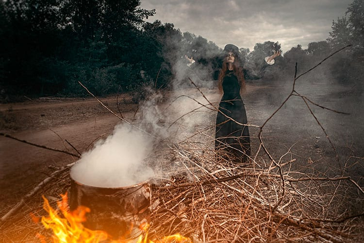 Witch standing behind a burning cauldron in the forest