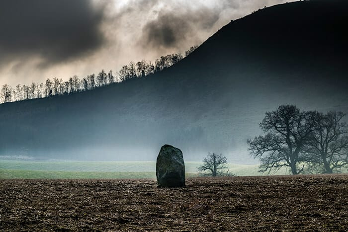 Single stone in the middle of a dark field surrounded in moss. Witches in Scotland may have been executed at this site.