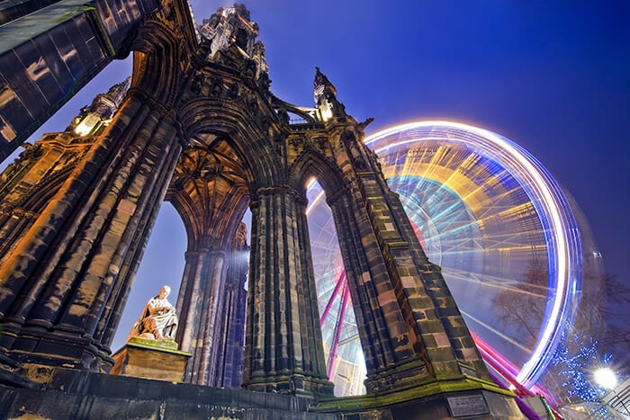 the Scott Monument in Edinburgh, looking up towards the gothic Victorian monument with the statue of Walter Scott in the middle of the monument and a ferris wheel behind the monument