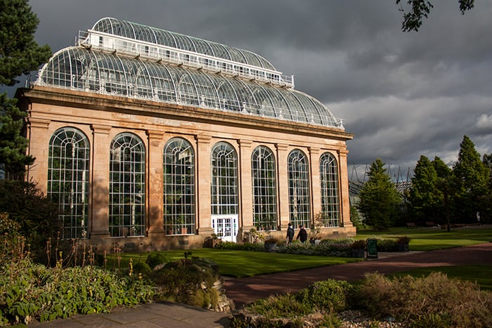 Outside of the Glass House at the Royal Botanic Garden in Edinburgh. The sun is shining onto the glass house building as a stormy grey sky appears behind the house.
