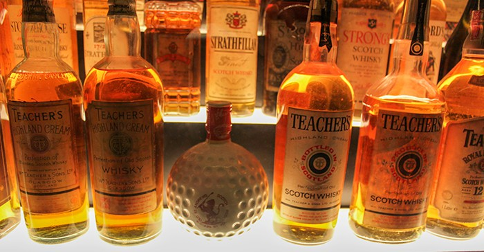 Golf ball shaped whisky bottle and normal bottles of whisky