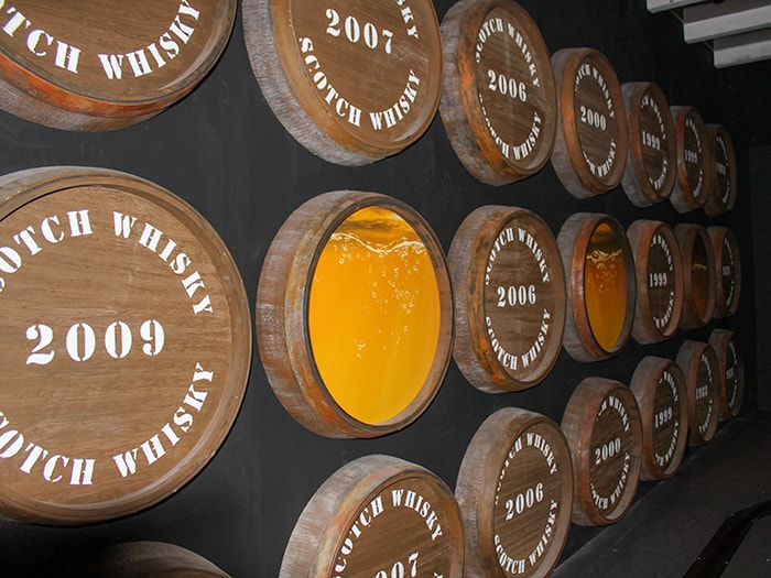 Scotch Whisky Barrels on the wall showing the color of each whisky by age
