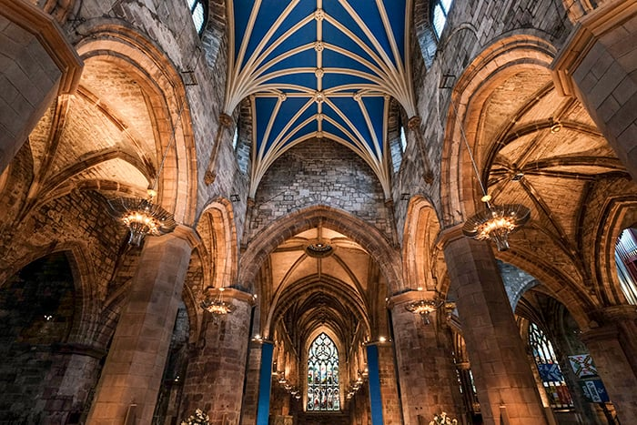 Interior of St Giles Cathedral in Edinburgh with the four columns, blue and gold ribbed ceiling and stained glass windows
