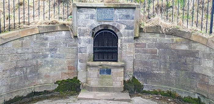 St. Margaret's Well at the bottom of Arthur's Seat in Edinburgh. A wall with a fountain like structure built into the wall underneath Arthur's Seat. The dark history at Holyrood Park in Edinburgh has ties with the well and witches.