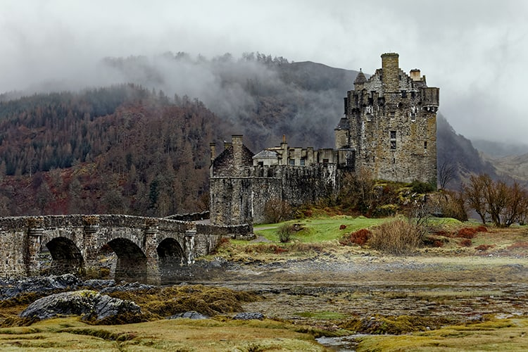 Famous Eilean Donan Castle in Spring misty morning. dark travel and spooky places to visit in Scotland.