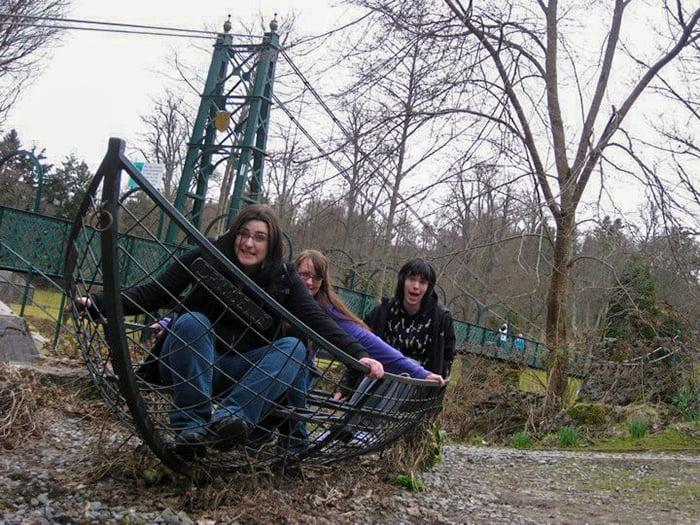 Three people sitting inside of a boat made of iron on land.