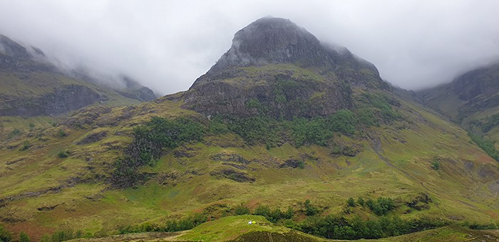 Glencoe in the Scottish Highlands, a glen filled with green grass and trees, with a munro sitting high in the sky with fog rolling in over the hill. Glencoe has dark history and is a spooky place to visit in Scotland because of it's dark tourism past.