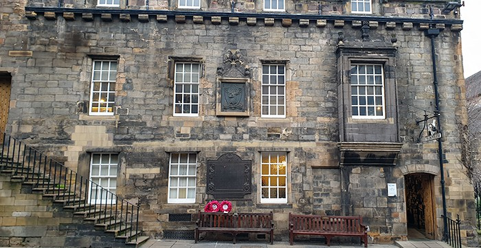 View of the old Canongate Tolbooth Building, stairs leading up on the left with two benches up against the building featuring a deer plaque and the entrance to The People's Story Museum on the right