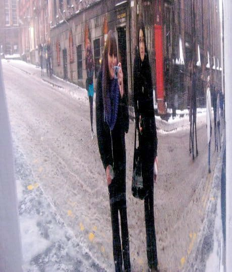 Two people standing in front of a wacky mirror on the Royal Mile in Edinburgh