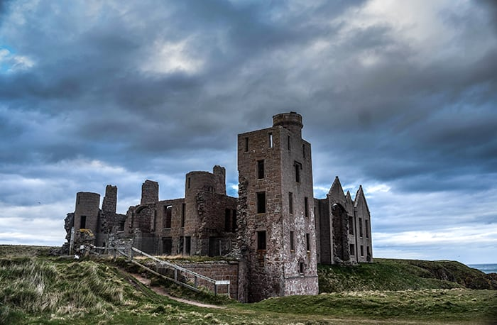 New Slains Castle, ruins and crumbled castle with all windows smashed out sitting on a hill with a stormy sky. One of the dark travel and spooky places to visit in Scotland.