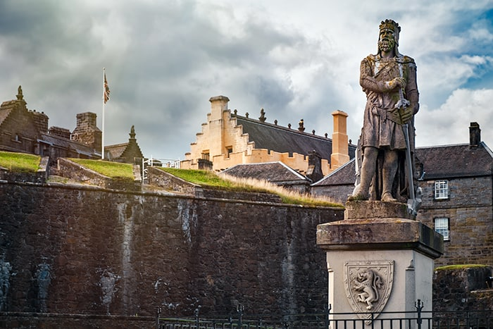Robert the Bruce Statue in front of Stirling Castle Walls in Scotland. The popular castle is a place of dark travel and spooky places to visit in Scotland.