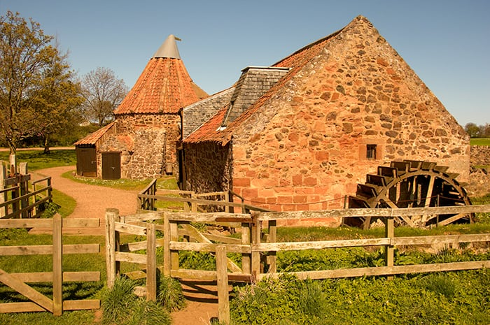 Old mill made of stone with a large water mill wheel in North Berwick Scotland