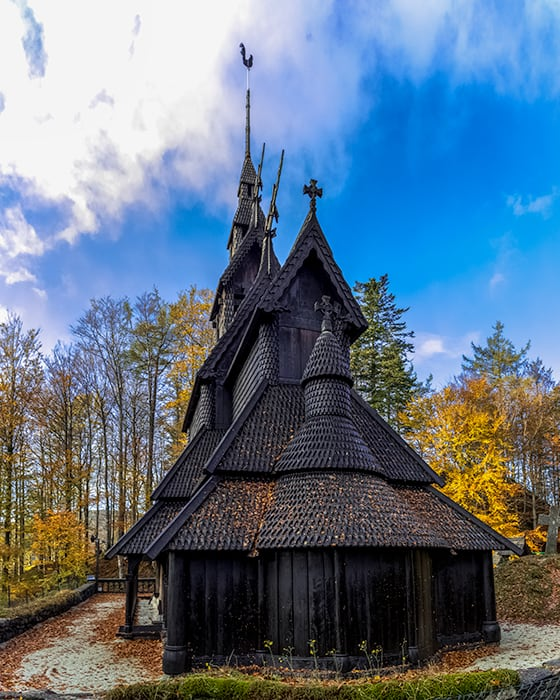 Fantoft Stave Church - Black Church in Norway, wood church painted black in the middle of the forest in Autumn