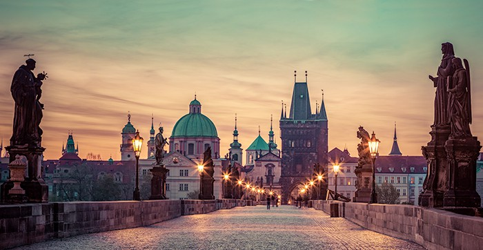 Charles Bridge in Prague with statues lining the outside, street lamps on and buildings of Prague in the background. The sky is green and orange.