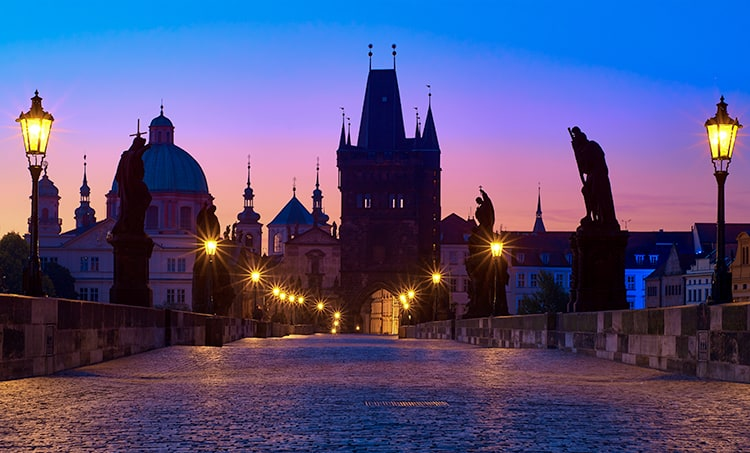 Charles Bridge in haunted Prague at dusk. Statues line the outside of the cobbled bridge with buildings in the background.