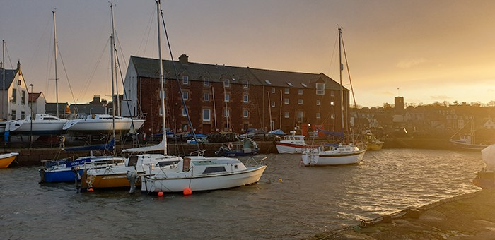 boats floating in the North Berwick Harbour at sunset
