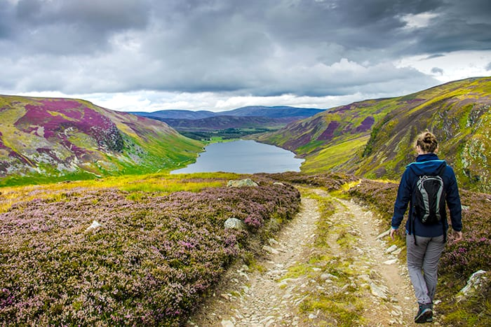 Hiking trail in Cairngorms National Park. Route down to Loch Lee, Angus, Scotland, UK. Woman wearing backpack walking down rocky trail towards a loch in the Scottish Highlands. What to pack for Scotland.