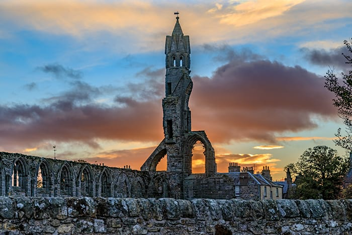 The ruins of Saint Andrews Cathedral, tower in the middle with the sun setting behind the building. The ghosts of St Andrews roam here.