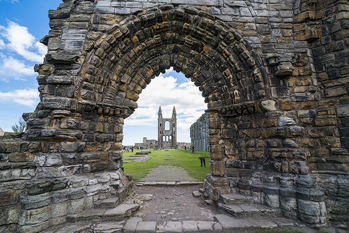 The ruins of Saint Andrews Cathedral through an archway in St. Andrews Scotland. The ghosts of St Andrews are seen roaming the ruins.
