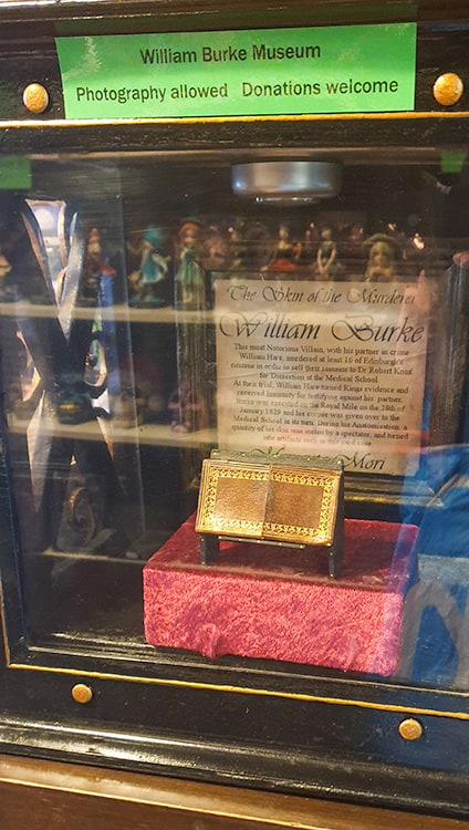 The skin of William Burke made into a wallet/card case on display behind glass.