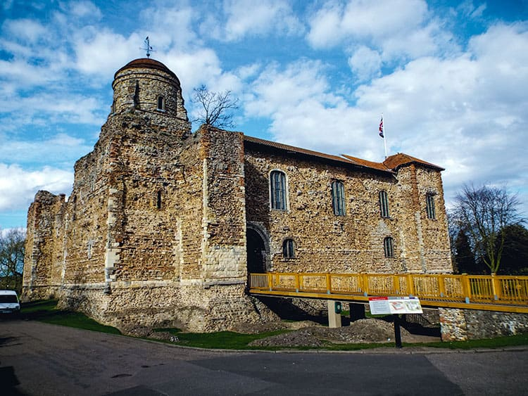 Colchester Castle is one of the Witch Trials in England sites. The castle sits in the centre of the picture with a yellow bridge on the right side.