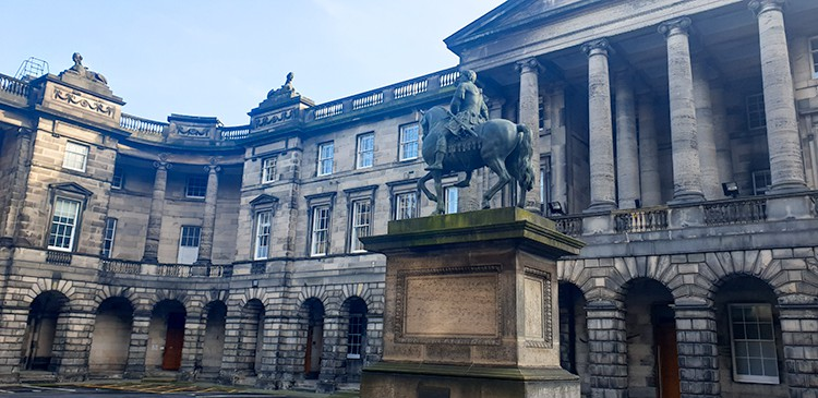 Large Parliament building with a statue of a man on a horse in the foreground.