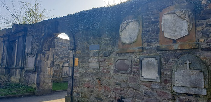 The Flodden wall and archway inside Greyfriars Kirkyard - the wall is lined with gravestones and vines.