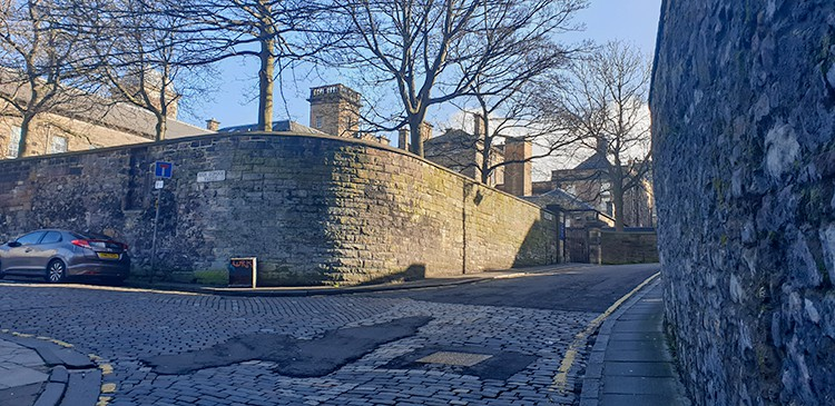 A crossing in a road with high brick walls on either side - the route Burke and Hare Edinburgh Tour took