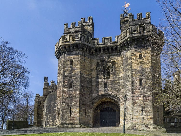 Lancaster Castle entrance, large turrets with a large door in the centre of the castle.