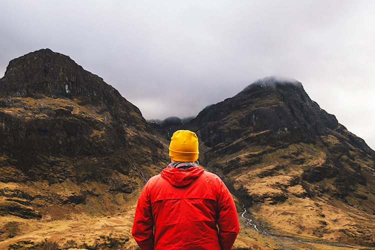 Man in a red coat and white hat looking towards the hills in Glencoe Scotland. What to expect when you move to Scotland? Incredible views.