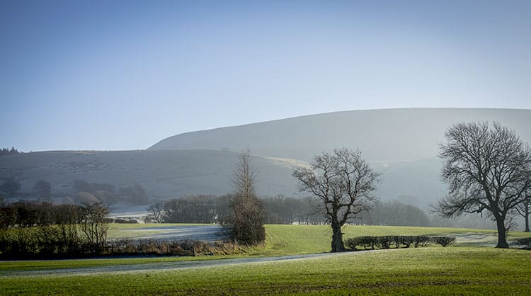 Quiet English Countryside with green grass, trees and the Pendle Hills in the background. One of the many Witch sites to visit in England .Witch Trials in England