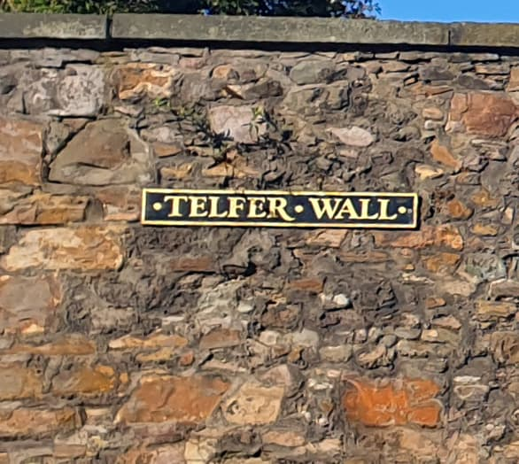 A brick and stone wall with the sight Telfer Wall