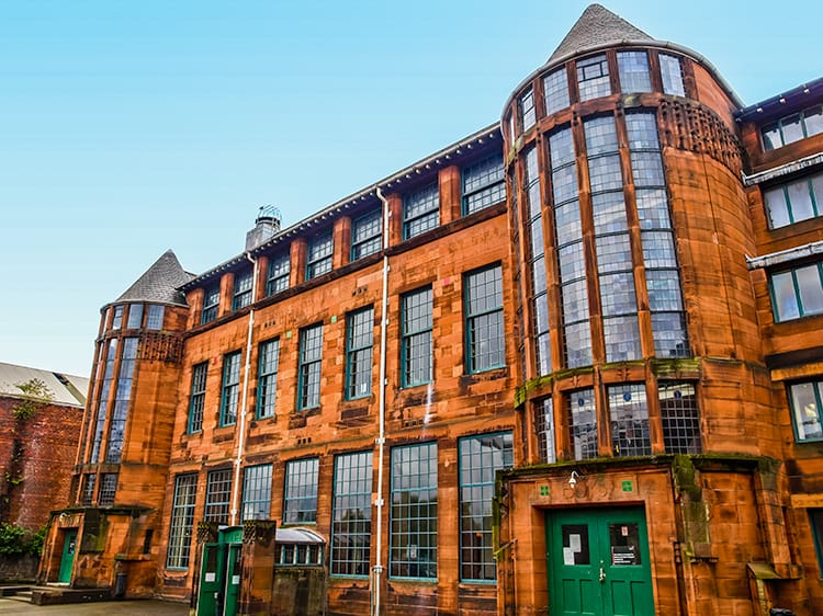 large orange brick building with windows and green door. The Scotland Street School Museum is one of the haunted places in Glasgow.
