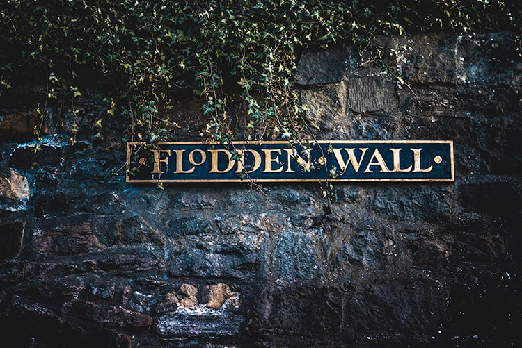 A medieval brick wall with a site that says Flodden Wall in gold writing. The wall and sign are partially covered in ivy.
