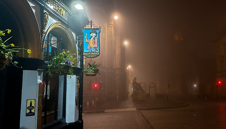 Deacon Brodie's Tavern with a foggy, misty Royal Mile at night. Deacon Brodie is one of the best haunted pubs in Edinburgh.