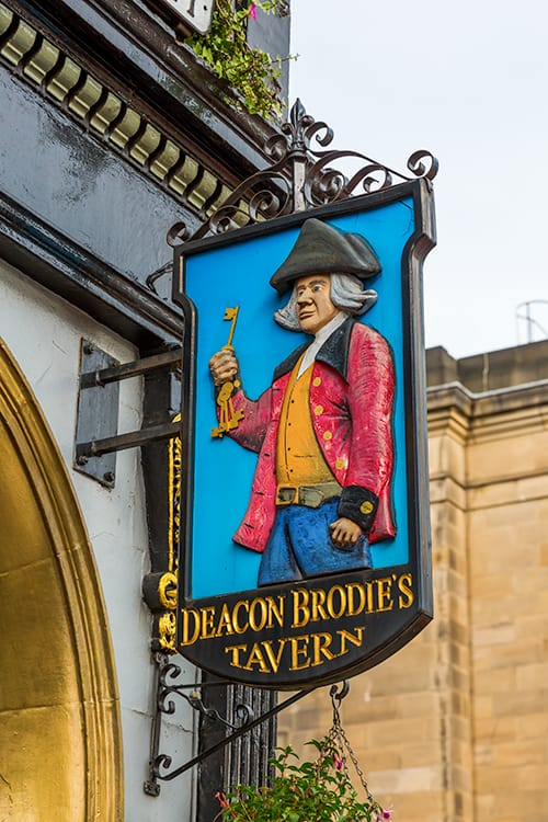 The sign for Deacon Brodie's Tavern in Edinburgh. Shows Deacon Brodie as a key maker. The Deacon Brodie Tavern is one of the best haunted pubs in Edinburgh.