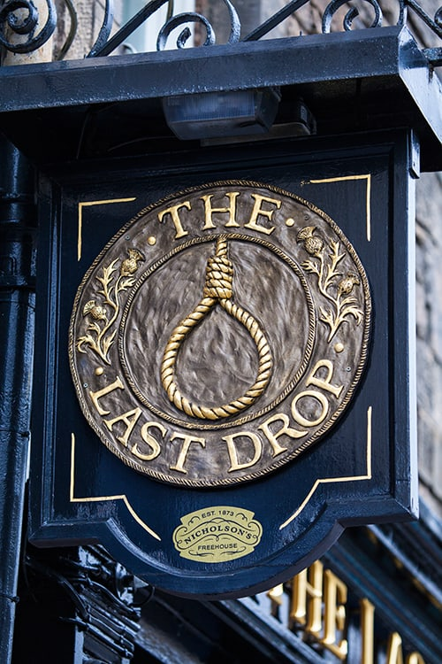 Closeup of the sign for the haunted Edinburgh pub - The Last Drop. The sign features an image of a noose outlined with the name of the pub. One of the best haunted pubs in Edinburgh