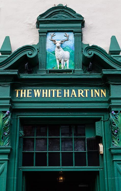 Green door frame with The White Hart Inn written in gold. A white deer with large green hills in the background sits above the door sign. Best haunted pubs in Edinburgh.