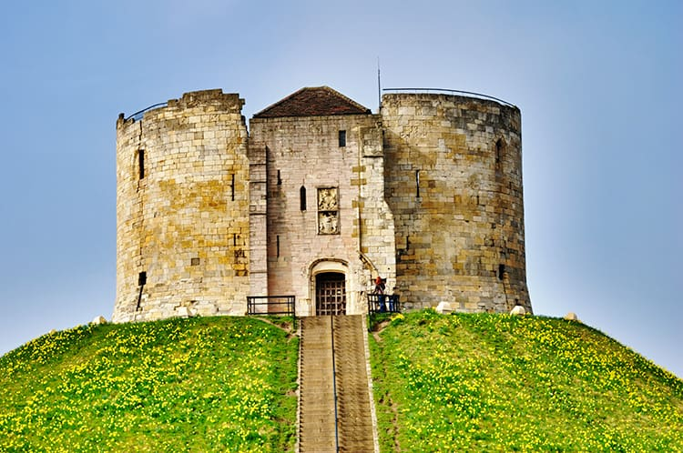 Medieval style round castle on a grassy hill. One of the dark history sites and haunted places in York, England.