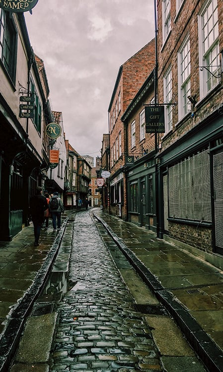 The Shambles is historic street lined with buildings and a very small cobble road in the center.